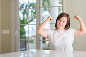 Down syndrome woman at home showing arms muscles smiling proud. Fitness concept. poster