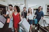 Company Of Friends Shopping In Mall With Packages. Shopping Concept. Girl In Red Dress. Woman In Whi poster