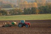 picture of cultivator-harrow  - Tractor plowing an agricultural field - JPG