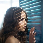 Sensual Woman With Makeup At Window. Beauty And Fashion Look. Fashion Woman With Makeup And Curly Ha poster
