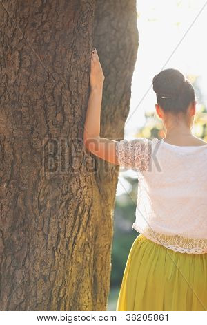 Young Woman Lean Against Tree. Rear View