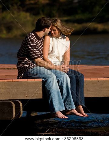 Young Couple In Love Sit Barefoot On Dock Over Lake