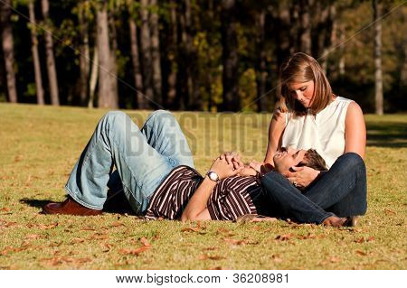Young Couple In Love Lay On Grassy Field