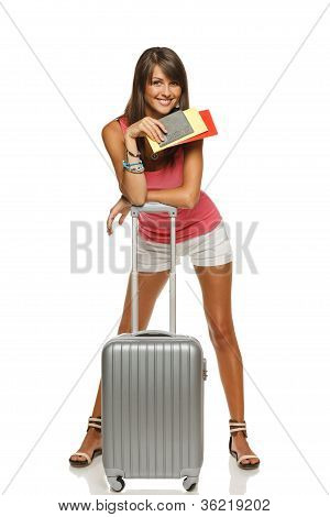 Young happy female standing with suitcase and tickets