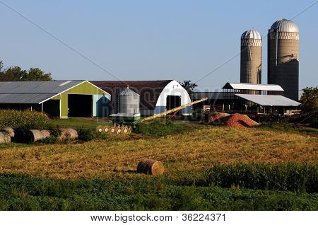 Farm In The Countryside With Farm Equipment, Machinery And Barn