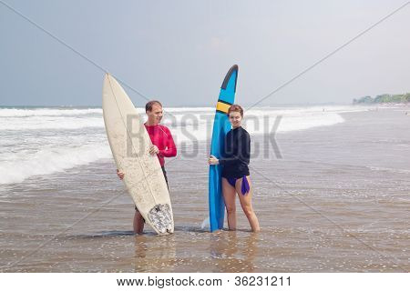Young people with surfboards stand in water