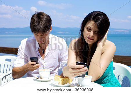 Couple Texting Having Breakfast In Front Of Lake