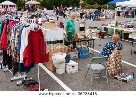 Consumidor escolhe através de mercadorias em venda de garagem da cidade