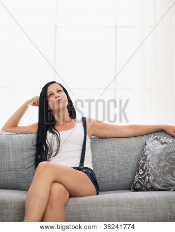 Thoughtful Girl Sitting On Couch In Living Room