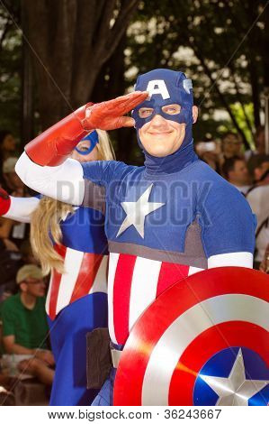 A comic book fan dressed as Captain American salutes at the annual DragonCon parade