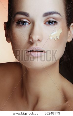Closeup portrait of beautiful woman with clean skin and natural make up applying tonal cream