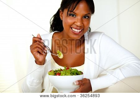 Smiling Young Woman Looking And Enjoying Salad