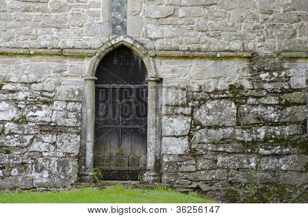 An Old Wooden Door, In The Stone Wall Of An Old 14Th Century Church