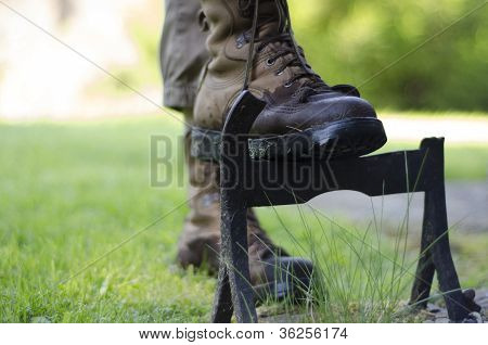 A Walker Cleaning The Soles  Of Walking Boots On An Old Cast Iron Boot Scraper.