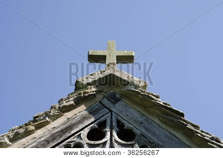 A Stone Cross On An Old, Carved, Wooden Church Porch
