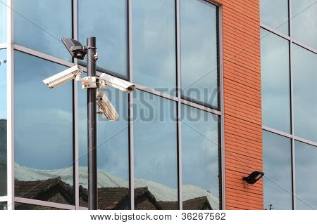 three security cameras on front of glass building