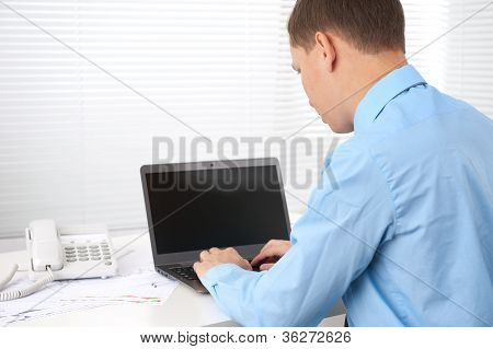 Rear View Of A Young Business Man Working Of A Laptop