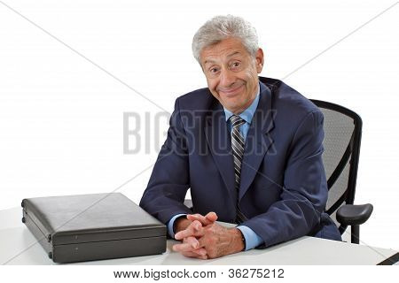 Cheerful Senior Business Man With Hands Folded On Desk
