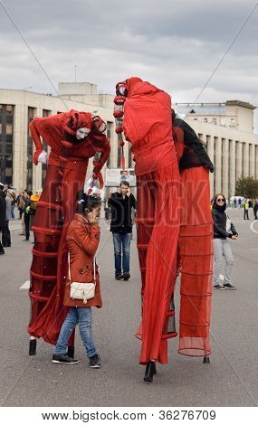 Moscow - September 1, 2012:people In Red Fancy-dress  Of Harlequin  Stay Near Girl In Red Dress Duri