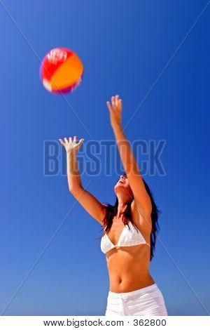 Girl Catching Beach Ball On Sunny Beach In Spain With Blue Sky