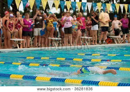 Youth Swimmer Swims Backstroke As Spectators Look On