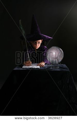 Wizard Boy Writing With A Feather Pen And Looking Into Crystal Ball