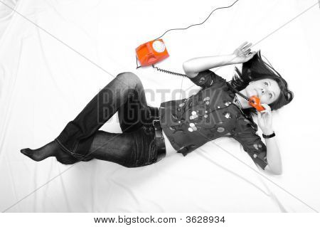 Pretty Girl Laying On The Floor And  Talking By Orange Phones