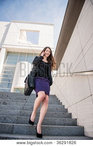 Business woman walking on stairs calling phone