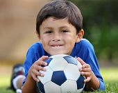 picture of playtime  - Young brown haired hispanic boy in blue shirt lying down on grass with soccer ball in hands - JPG
