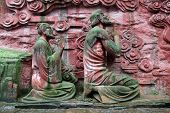 image of emei  - Statues of monks near the wall in Emeishan - JPG