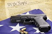 image of handguns  - A 45 caliber handgun and ammunition resting on a folded flag against the United States constitution - JPG