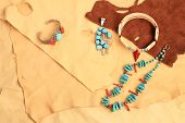 stock photo of buckskin  - Assortment of Native American silver turquoise and coral jewelry displayed on pieces of soft and pliable buckskin and leather - JPG
