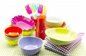 picture of nacked  - Colorful plastic tableware stacked next to each other surrounded by white background - JPG