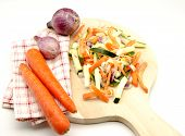 stock photo of crudites  - Assorted vegetables cut on a table wood surrounded by white background - JPG