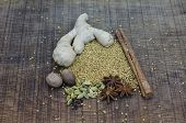 stock photo of vedic  - A selection of spices used in an ayurveda diet and healing with root ginger a cinnamon stick cardamon pods and seeds nutmegs and fenugreek seeds scattered on an oak wood surface - JPG