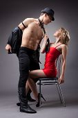 stock photo of striptease  - strong man show striptease for sexy woman in red - JPG