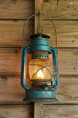 picture of glowing  - Rusty lit blue lantern hanging in an old shed - JPG