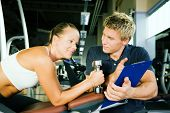 stock photo of gym workout  - Woman with dumbbells in a gym her personal trainer gives a report on training - JPG