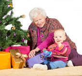 image of babysitting  - Grandmother babysitting young baby sitting together on the floor alongside a decorated Christmas tree and giftwrapped presents - JPG