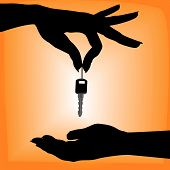 image of car key  - A silhouette female hand holds an auto key over a cupped hand against an orange background - JPG