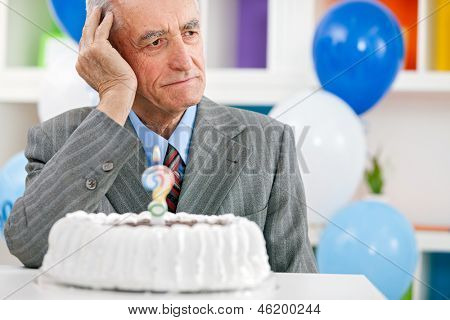 Senior man sitting front of birthday cake and trying to remember how old is