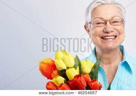 Happy grandmother holding bouquet of tulips at mother's day, smiling.
