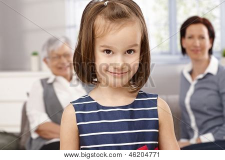 Closeup portrait of cute little girl, mother and grandmother watching from background.