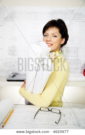 Female Engineer With Blueprints In The Office