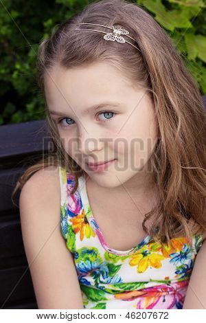 Beautiful Young Girl Is Sitting On The Bench