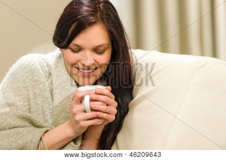 Smiling woman enjoying hot tea sitting on couch