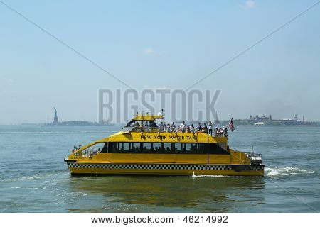 New York City Water Taxi in the front of Statue of Liberty and Ellis Island