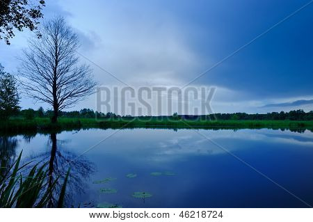 Calm Lake And Dark Blue Sky In The Evening