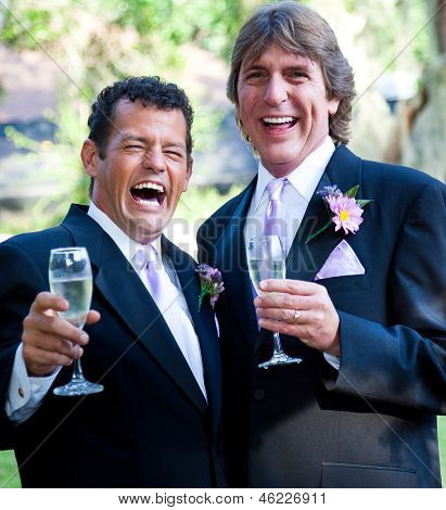 Happy gay wedding couple enjoying champagne and laughing.