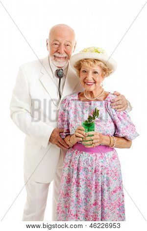 Portrait of beautiful Southern senior couple dressed for Kentucky Derby Day or a party and holding a mint julep.